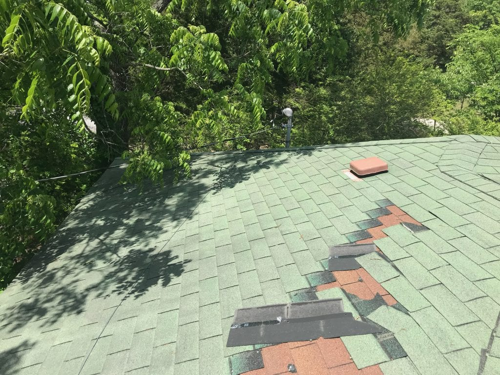wind damaged shingles on a house. two layers of three tab shingles