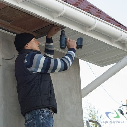 Worker installing vinyl soffit after restoration of extensive storm damage on a stucco house, using power drill. House has upgraded rounded gutters and vinyl fascia