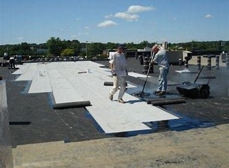 White built-up roofing being installed with rollers and roofers
