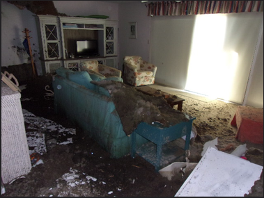 Bedroom with ceiling debris fallen on bed due to leaking roof and water damage