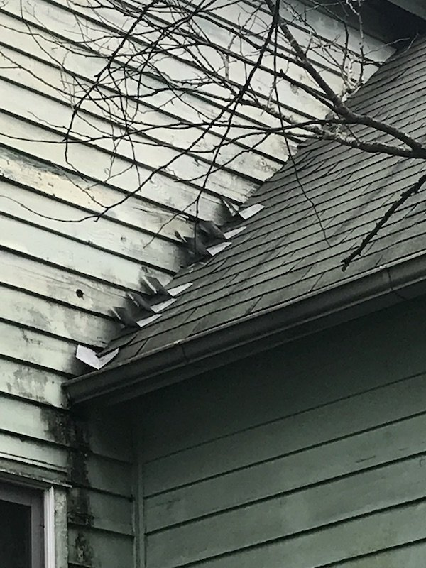 Botched flashing and siding is too close to the shingles. You can see the damage under the eaves