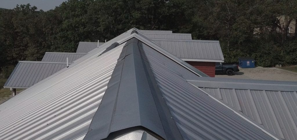 Condo complex with panel metal roofing, some of the ridge is bent
