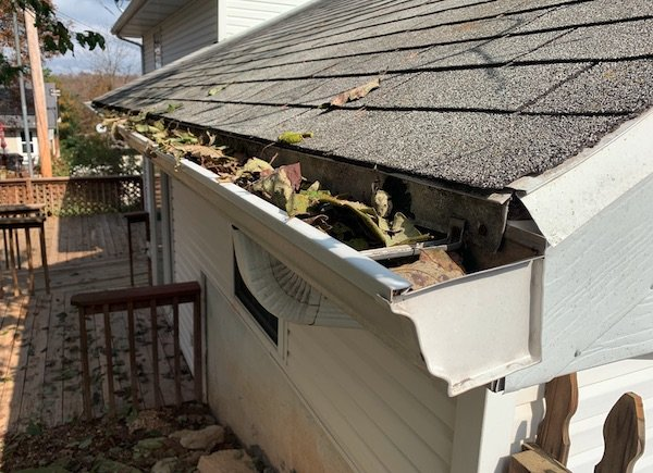 Gutter with leaves that needs to be cleaned out