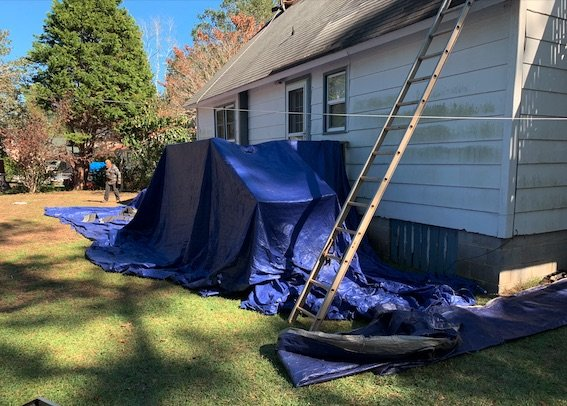 House getting roof replacement with tarping covering the rear porch and deck and landscaping