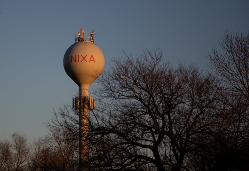 Water tower in Nixa at sunset with trees