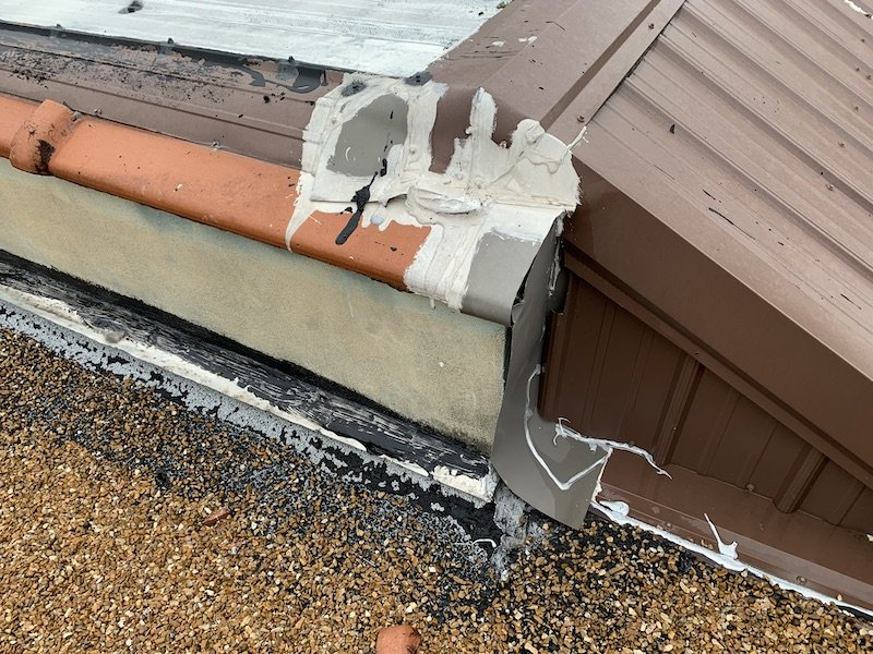 metal roof flashing at parapet wall with a lot of caulking and gaps