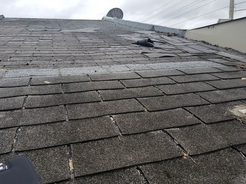 shingles blown aside on convenience store roof with two layers of 3-tab shingles
