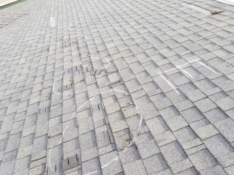 missing shingle tabs and creased shingles damaged by wind