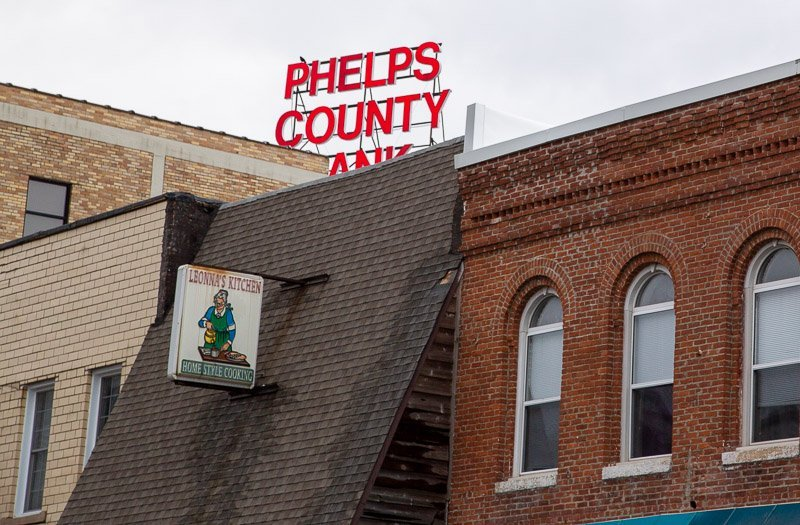 Steep roof with damaged shingles near edge in downtown Rolla MO